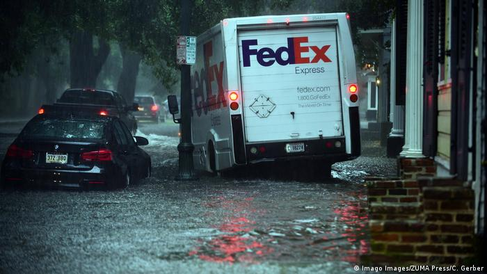 A FedEx truck drives on the sidewalk in the French Quarter to get around stalled cars after heavy rain flooded streets and businesses ahead of Tropical Depression Barry