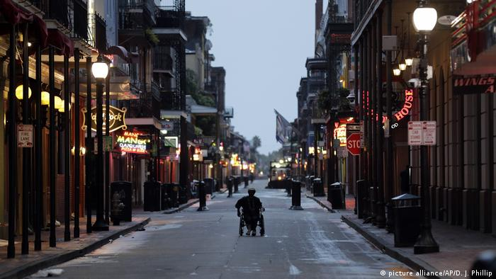 A man in a wheelchair makes his way down Bourbon Street in the French Quarter