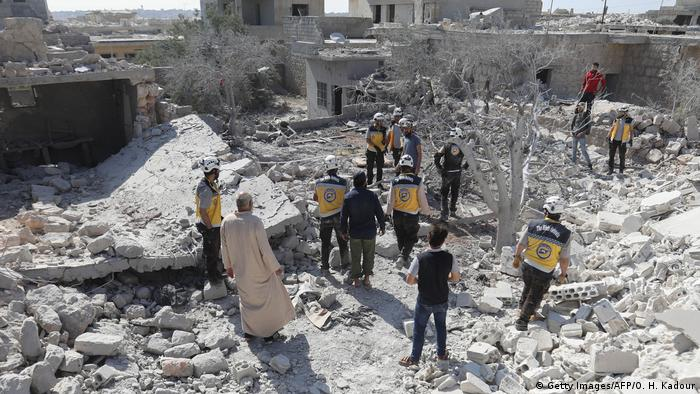 People gather amid the rubble left by an airstrike