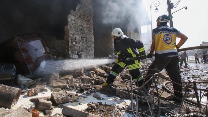 Члены организации Сирийская гражданская оборона (Белые каски) разбирают развалины в провинции Идлиб после авиаудара правительсвенных войск (фото из архива)