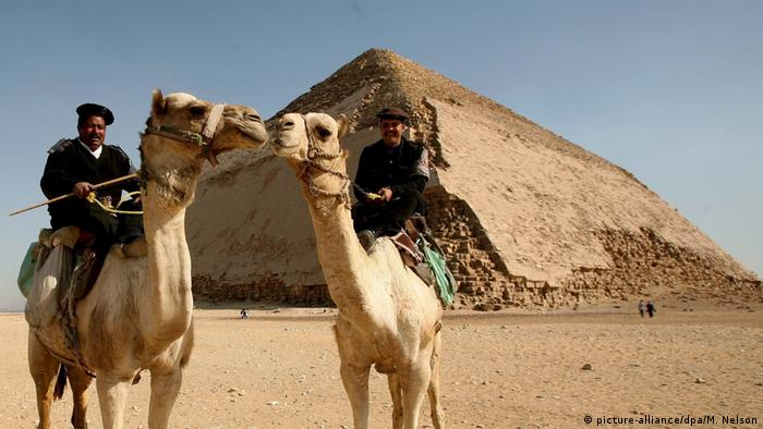 Men on camels standing in fron of Egypt's Bent Pyramid (picture-alliance/dpa/M. Nelson)