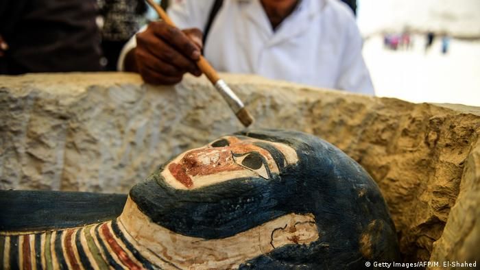 A man brushes dust off a sarcaphogus discovered in Egypt (Getty Images/AFP/M. El-Shahed)