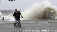 Jeff Holland rides his bike through waters pushed over the seawall from Lake Pontchartrain by winds from Tropical Storm Barry Saturday, July 13, 2019, in Mandeville, La. (AP Photo/David J. Phillip) |