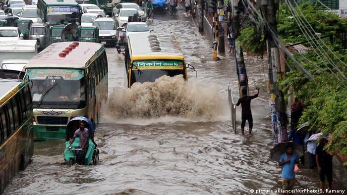 Rickshaw passengers being rescued in Dhaka, Bangladesh (picture-alliance/NurPhoto/S. Ramany)
