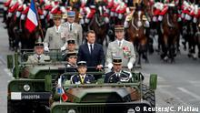 14.07.2019 French President Emmanuel Macron and Chief of the Defense Staff of the French Army General Francois Lecointre arrive in a command car for the traditional Bastille Day military parade on the Champs-Elysees Avenue in Paris, France, July 14, 2019. REUTERS/Charles Platiau