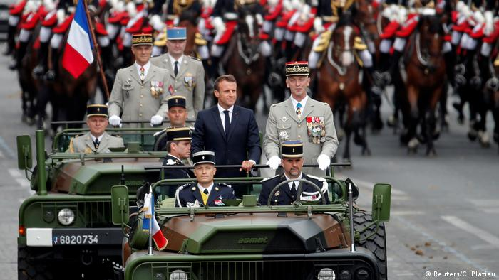 France's President Emmanuel Maron rides in an open military vehicle during the Bastille Day parade
