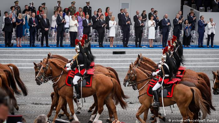 Merkel stood to review the troops passing in Paris