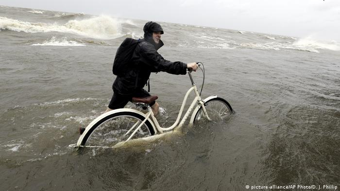 Tyler Holland guides his bike through the water as winds from Tropical Storm Barry push water from Lake Pontchartrain over the seawall
