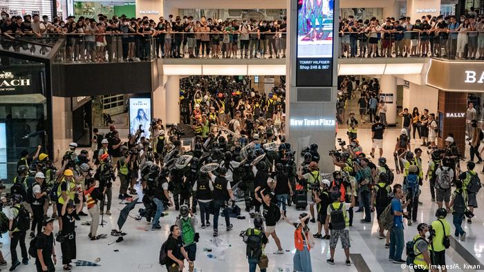 Riot police chase protesters through a shopping mall as they clash with protesters after taking part in a pro-democracy march on July 14, 2019 in Hong Kong