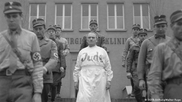 Filmstill aus Professor Mamlock, mit PM, der in Arztkittel mit Aufschrift Jude zwischen Nazis abgeführt wird (DEFA-Stiftung/Walter Ruge)