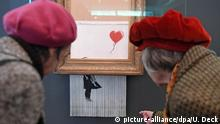 Two women look at a shredded paiting, half of which hangs out from the frame.