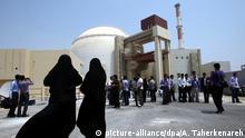 ARCHIV - 21.08.2010, Iran, Buschehr: Zwei weibliche Sicherheitsbeamte stehen vor dem Atomkraftwerk Buschehr und beobachten Medienvertreter. Zum Jahrestag des US-Ausstiegs aus dem internationalen Atomabkommen mit dem Iran hat der iranische Präsident Ruhani einen Teilausstieg seines Landes aus dem Deal bekanntgegeben. Foto: Abedin Taherkenareh/EPA/dpa +++ dpa-Bildfunk +++  