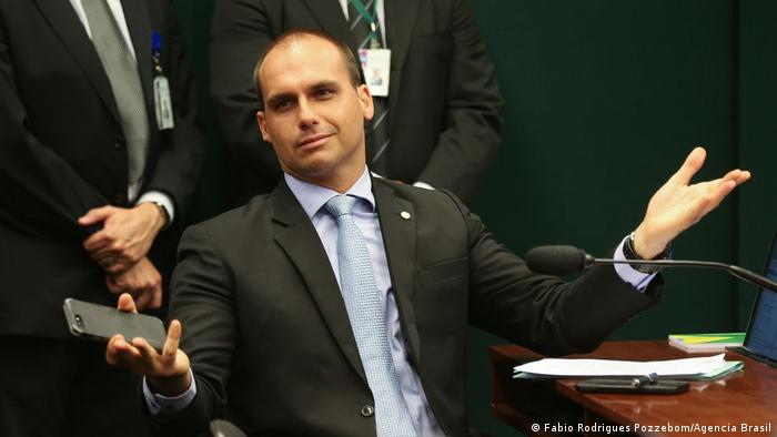 Eduardo Bolsonaro, son of Brazilian President Jair Bolsonaro, holds out his hands in a gesture while sitting at a desk (Fabio Rodrigues Pozzebom/Agencia Brasil)
