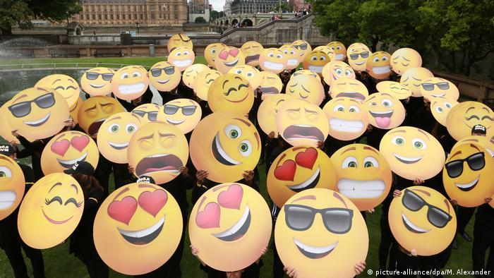 People hold up emoji signs