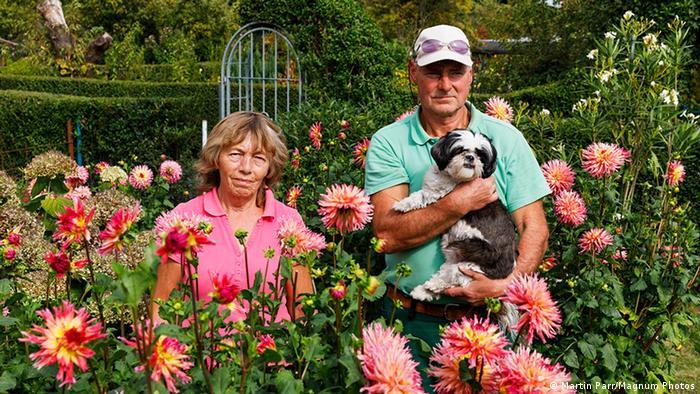 Eine Frau und ein Mann stehen in ihrem Kleingarten, der Mann hält einen Hund auf dem Arm. (Martin Parr/Magnum Photos)