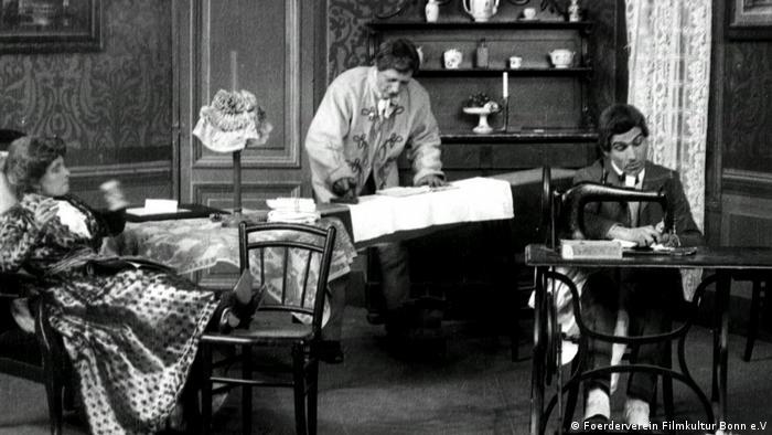 Filmstill von Alice Guy Emanzipation der Frauen Szene mit Frau im Stuhl und arbeitenden Männern (Foerderverein Filmkultur Bonn e.V)