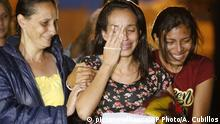 Karen Palacios, center, is helped by family members after she was released from prison at Los Teques on the outskirts of Caracas, Venezuela, Tuesday, July 16, 2019. Palacios who plays the clarinet and was cut from the National Philharmonic for criticizing the government, was detained for 6 weeks. (AP Photo/Ariana Cubillos) |