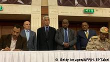 Sudanese deputy chief of the ruling miliary council Mohamed Hamdan Dagalo (R) and a protest leader (L) ink an agreement before AU and Ethiopian mediators in Khartoum early on July 17, 2019. - Sudan's protesters and ruling generals inked a power sharing deal, paving the way for a civilian administration, a key demand of demonstrators since president Omar al-Bashir was deposed in April. The two sides initialled a document called the Political Declaration, an AFP correspondent reported, after intense talks through the night over fine details of the agreement. (Photo by Haitham EL-TABEI / AFP) (Photo credit should read HAITHAM EL-TABEI/AFP/Getty Images)