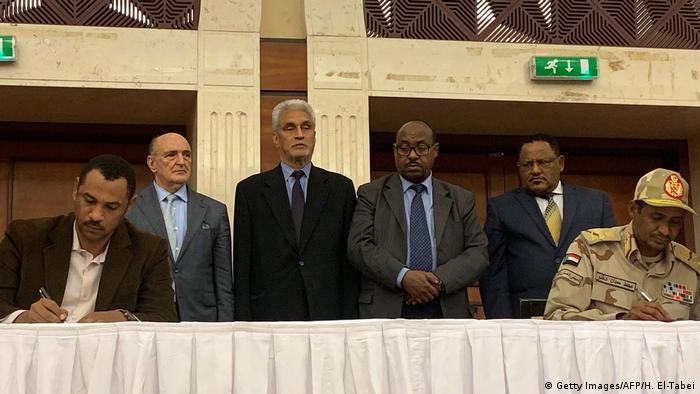 Representante do movimento de contestação (esq.) e líder dos militares, o general Mohammed Hamdan Dagalo (dir.), assinam acordo em Cartum
