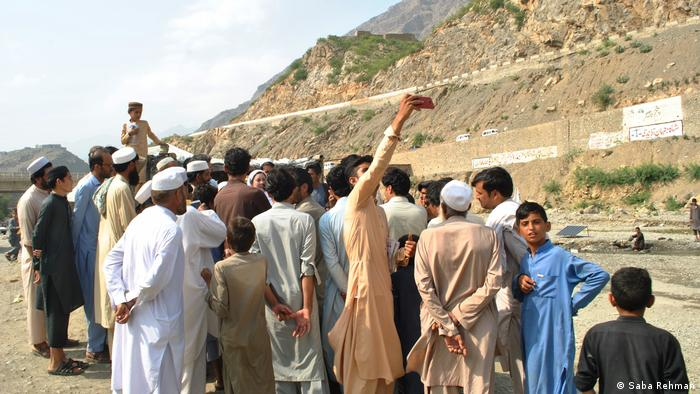 A young man takes a selfie with Naheed Afridi at a market in Khyber District
