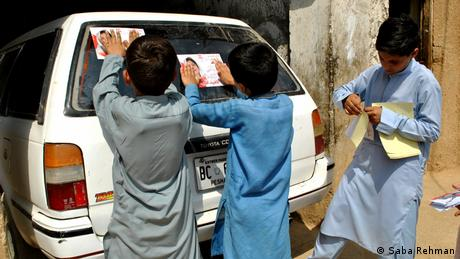 Boys paste Naheed Afridi campaign stickers on a car