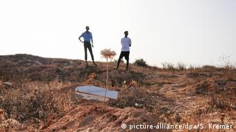 Sandy hill, a coffin and a tree with two men in the background (picture-alliance/dpa/S. Kremer)