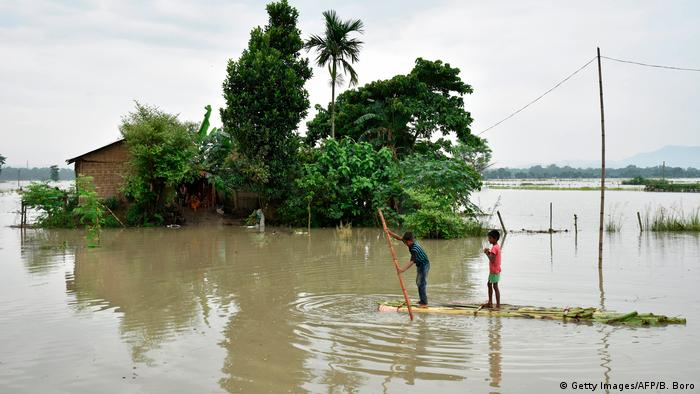 Two men paddle accross a flood on a makeshift raft