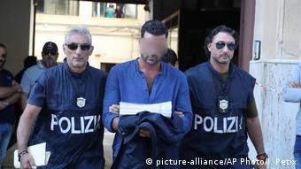 Итальянские полицейские ведут предполагаемого члена мафиозной группировки