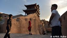 This photo taken on June 3, 2019 shows people taking photos in the restored old city area of Kashgar, in China's western Xinjiang region. - In China's Xinjiang, a northwest region tightly controlled by police, authorities have created a parallel universe for tourists and locals -- a place where travellers sightsee just a stone's throw from internment camps. (Photo by GREG BAKER / AFP) / TO GO WITH: China-rights-tourism-Xinjiang, FEATURE by Eva XIAO