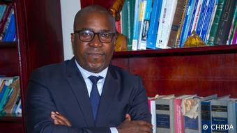Co-author Felix Agbor Balla stands in front of a bookcase