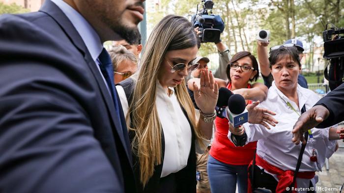 Woman walks through crowd of journalists