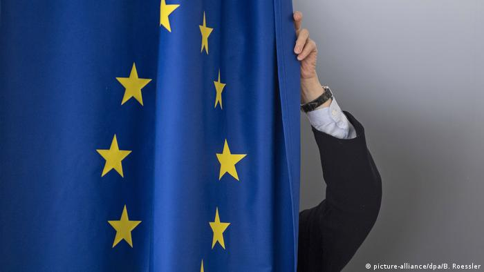 A person's hand straightening an EU flag (picture-alliance/dpa/B. Roessler)
