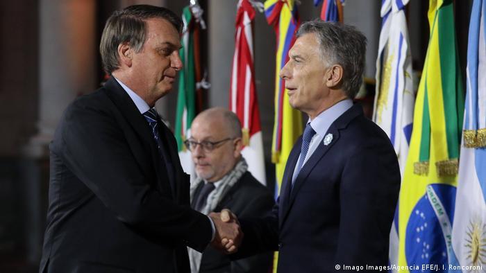 Jair Bolsonaro and Mauricio Macri shake hands at a Mercosur summit in Argentina