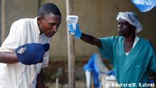 FILE PHOTO: A health worker measures the temperature of a man entering the ALIMA (The Alliance for International Medical Action) Ebola treatment centre in Beni, in the Democratic Republic of Congo, April 1, 2019. REUTERS/Baz Ratner/File Photo