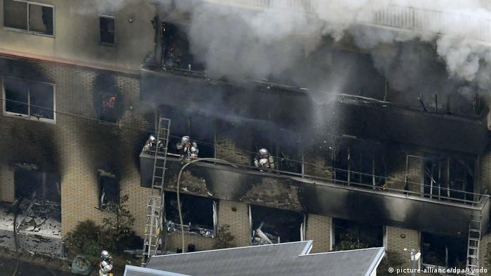 Firefighters use ladders to access the upper levels of the burning film studio
