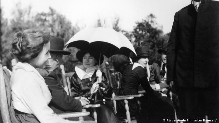 Regisseurin Alice Guy beim Dreh, in einem Stuhl, mit Sonnenschirm (Förderverein Filmkultur Bonn e.V.)