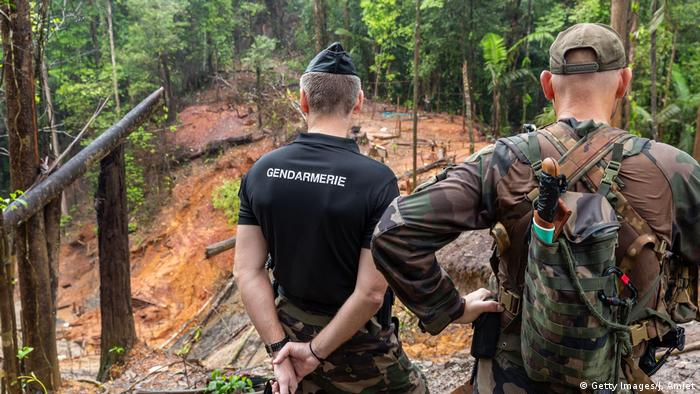 French gendarmes and members of WWF inspect an illegal gold-mining site