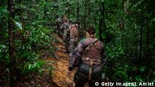 French gendarmes walk throught the jungle before arriving on an illegal gold panning site near the village of Cacao, 60 kms from the capital Cayenne, French overseas department of Guiana, on June 10, 2019. - The Guiana's biodiversity is threatened by illegal gold panning, AFP reports. (Photo by jody amiet / AFP) (Photo credit should read JODY AMIET/AFP/Getty Images)
