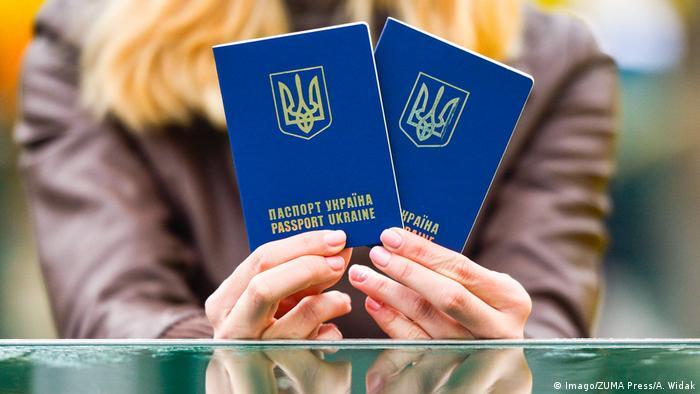 Девушка держит в руках два украинских паспорта