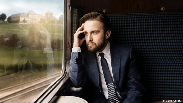 Daniil Trifonov with suit and tie sits in a train car and watches the landscape pass by (Dario Acosta)