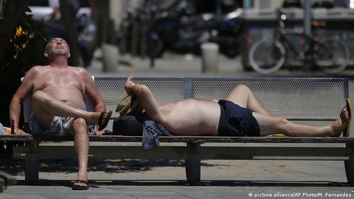 Two man enjoy the sun at Barceloneta beach during a heat wave in Barcelona, Spain