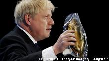 Boris Johnson holds up a kipper (picture-alliance/AP Images/F. Augstein)