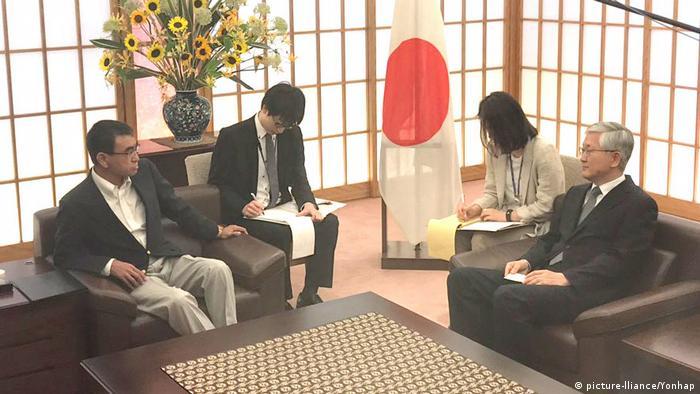 South Korean Ambassador Nam Gwan-pyo (R) talks with Japanese Foreign Minister Taro Kono
