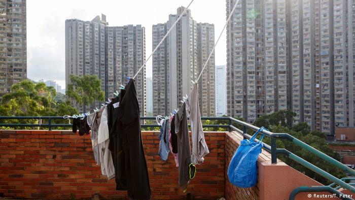 Постиранная одежда сушится на веревке на фоне небоскребов Гонконга