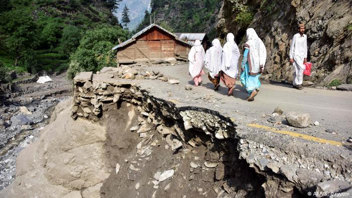 Pessoas com lenços brancos na cabeça caminhando ao longo de estrada destruída