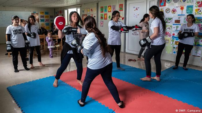 Husna Said Yusef holds her gloves up while another girl practices a combination of different punches as she walks forward across the mat