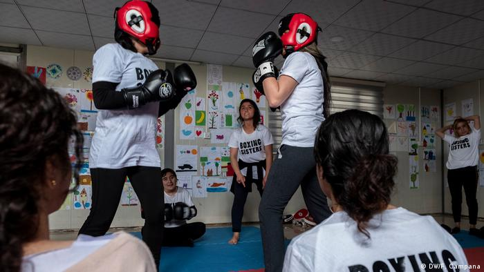Two girls Yazidi girls spar with each other while Husna Said Yusef coaches them
