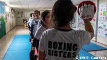 März 2019 Yazidi women and girls stand in a line as they take turns one-by-one hitting the upheld boxing gloves of Husna Said Yusef.