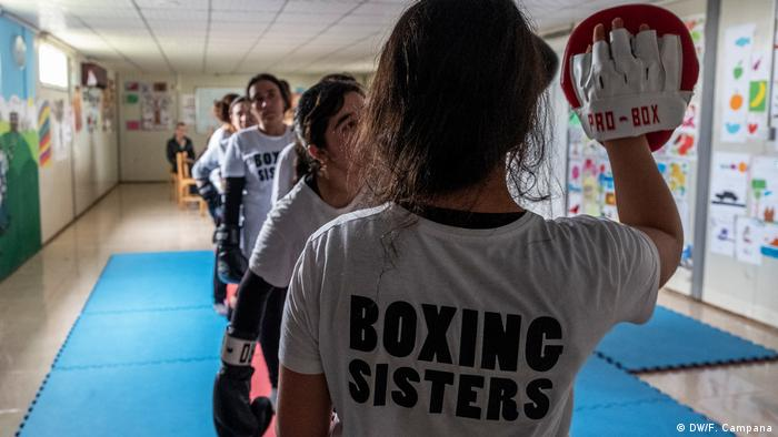 Yazidi women stand in line as they take turns hitting the upheld boxing gloves of Husna Said Yusef