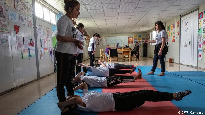 Yazidi women and girls do abdominal exercises to warm up before boxing class.